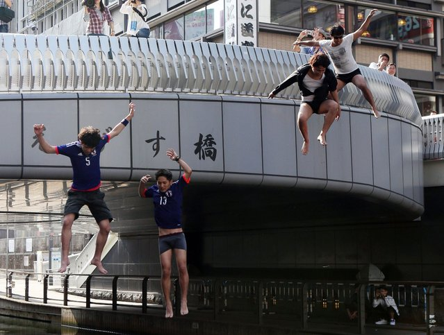 Japanese football supporters jump into a river in Osaka on June 25, 2014 after Japan was defeated by Colombia at the FIFA World Cup group C match in Brazil. (Photo by AFP Photo/JIJI Press)