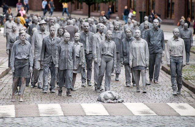 """Prostestors dressed in grey clothes like Zombies attend a arts performance called """"1000 Gestalten"""" demonstration prior the upcoming G20 summit in Hamburg, northern Germany, 05 July 2017. (Photo by Lukas Barth-Tuttas/EPA)"""