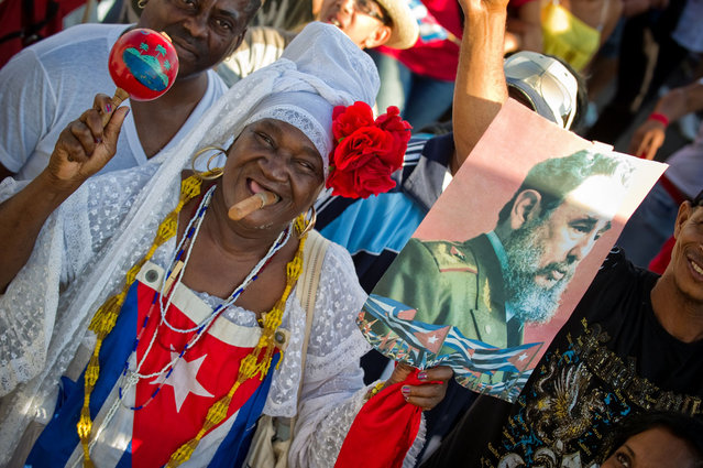 "A woman carries a poster of former Cuban President Fidel Castro as thousands of Cubans march under the slogan ""Preserve and Perfect Socialism"", at Revolution Square in Havana during Labour Day on May 1, 2012"