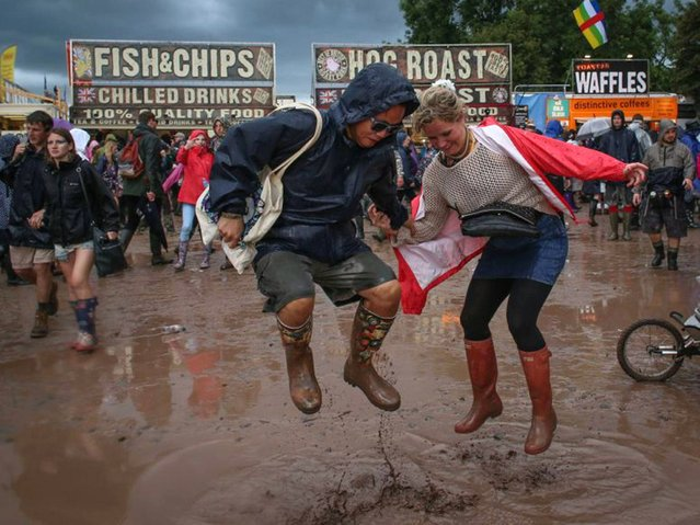 Festival goers jump in mud at Worthy Farm in Pilton during the 2014 Glastonbury Festival on June 27, 2014 in Glastonbury, England. (Photo by Matt Cardy/Getty Images)