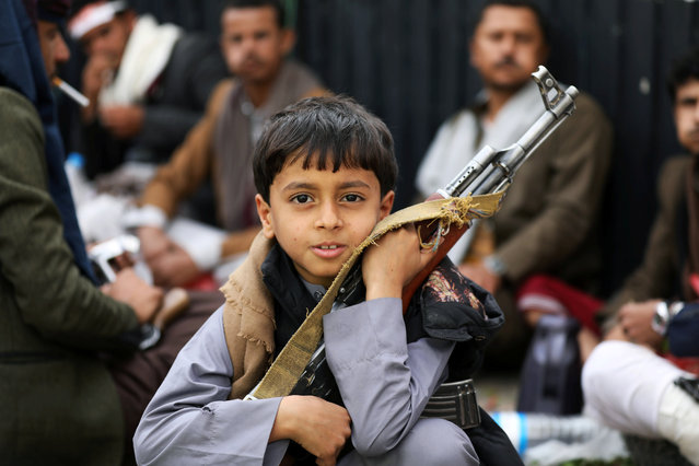 A boy holds a rifle as he attends a rally of Houthi movement supporters to mark the Ashura in Sanaa, Yemen on September 10, 2019. (Photo by Khaled Abdullah/Reuters)