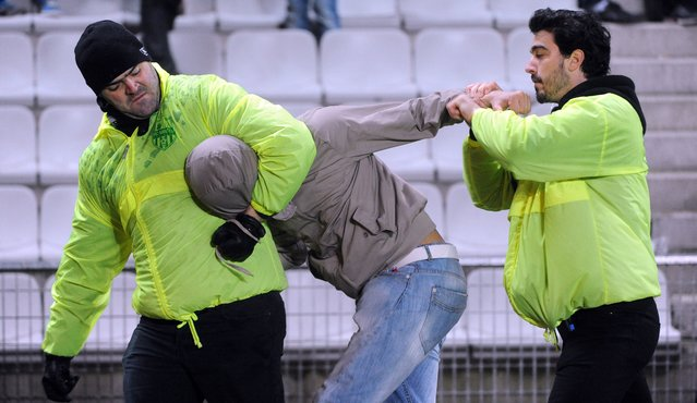 A dressed streaker is arrested after running on the field during the French League Cup football match between Nantes and Paris Saint-Germain at the La Beaujoire stadium in Nantes, western France, on February 4, 2014. (Photo by Jean-Francois Monier/AFP Photo)