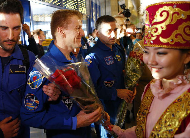 The International Space Station crew, Britain's Tim Peake, second left, Russia's Yuri Malenchenko, third left, and Tim Kopra of US, fourth left, receive flowers during a welcoming ceremony at the airport of Karaganda, Kazakhstan, Saturday, June 18, 2016. (Photo by Shamil Zhumatov/Pool Photo via AP Photo)