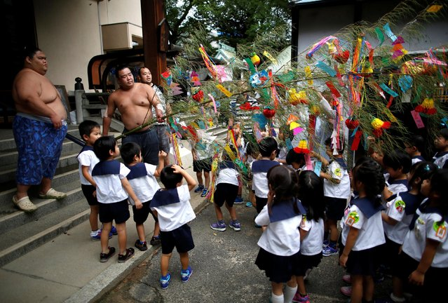 Tanabata festival decorations, made with a bamboo branch and strips of coloured paper, often with people's wishes written on them, are presented to sumo wrestlers from kindergarteners in Nagoya, Japan on July 18, 2017. (Photo by Issei Kato/Reuters)