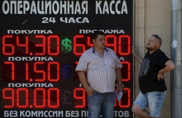 Men stand next to a board showing currency exchange rates of the U.S. dollar, euro, and British pound (top-bottom) against the rouble in Moscow, Russia, August 12, 2015. The Russian rouble hit a six-month low on Wednesday, tracking down lower oil prices and ignoring a central bank statement saying that the devaluation of the Chinese yuan may ultimately benefit the rouble. (Photo by Sergei Karpukhin/Reuters)