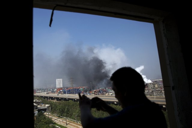 A man takes pictures from inside a damaged residential building towards the site of the explosions at the Binhai new district, Tianjin, August 13, 2015. (Photo by Damir Sagolj/Reuters)