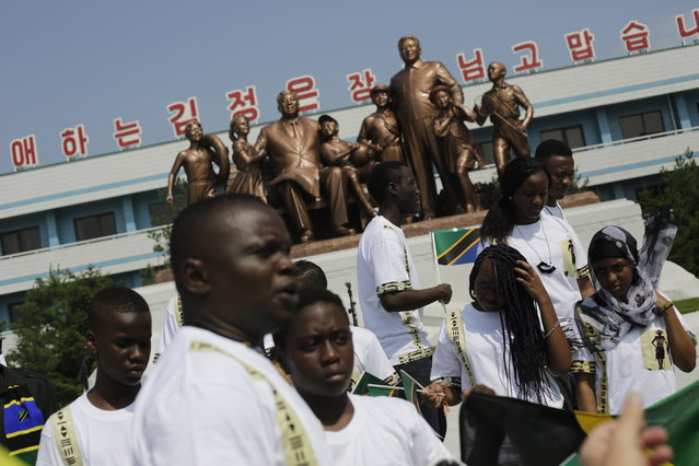 Students from the Laureat International School in Tanzania walk past a statue of the late North Korean leaders Kim Il Sung and Kim Jong Il, surrounded by children, on the parade square of the Songdowon International Children's Camp, Tuesday, July 29, 2014, in Wonsan, North Korea. The camp, which has been operating for nearly 30 years, was originally intended mainly to deepen relations with friendly countries in the Communist or non-aligned world. But officials say they are willing to accept youth from anywhere – even the United States. (Photo by Wong Maye-E/AP Photo)