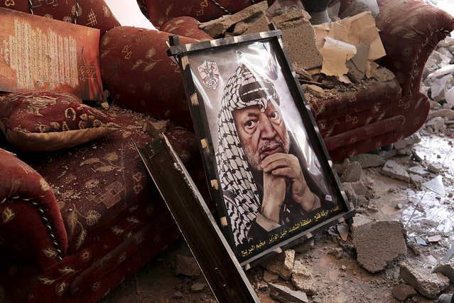 A poster of the late Palestinian leader Yasser Arafat sits in the rubble of a destroyed house in the Bureij refugee camp in the central Gaza Strip, on August 1, 2014. (Photo by Adel Hana/Associated Press)