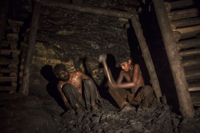 Samiullah (R), who says he is 14-years-old, breaks coal inside a mine in Choa Saidan Shah, Punjab province, April 29, 2014. (Photo by Sara Farid/Reuters)