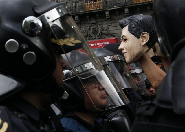 A member of the National Coordinator of Workers of Education of Mexico (CNTE) holds a mask resembling Mexican President Enrique Pena Nieto, surrounded by policemen, during a protest against the education reform, in Mexico City, Mexico, 05 July 2016. The CNTE, a union with its biggest support in the poorest states, Oaxaca, Michoacan, Guerrero, is battling for the abolition of an education reform enacted by Mexican Government in 2013. (Photo by Jorge Nunez/EPA)