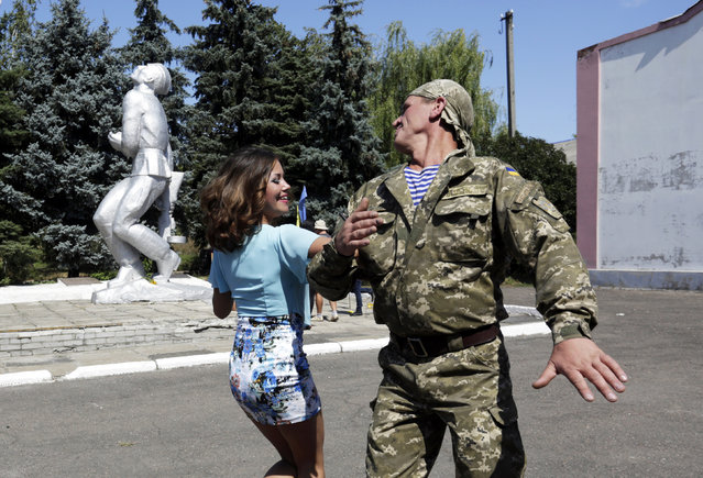 An Ukrainian serviceman dance with a woman during an open air celebrations of the Independence Day of Ukraine in Novoselivka village, some 20 km from Donetsk, on August 23, 2015. Ukraine will mark the Independence Day on August 24, 2015. (Photo by Anatolii Stepanov/AFP Photo)
