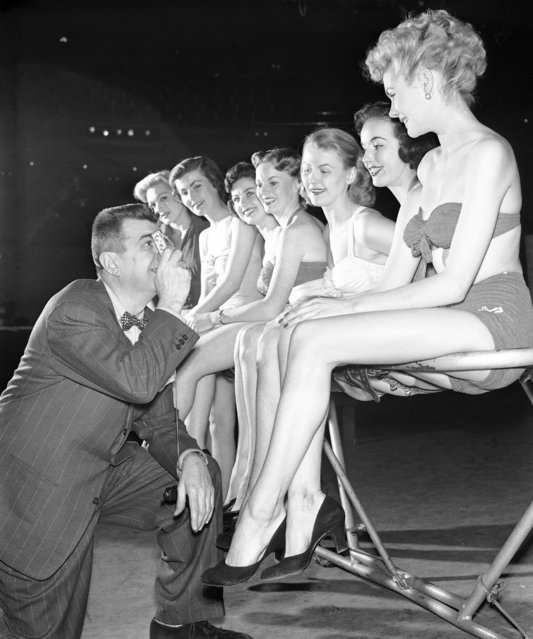 Ken Murray, stage and television comedian, uses a tiny precision camera to aid him in selecting young women for his soon-to-come television program, at a CBS studio in New York, Jan. 22, 1952. The girls are: front to back, Bettina Edwards of Beverly, Mass.; Joan Fetherston, New York; Doris Keith, Scarsdale, NY.; Peggy O'Neil, New York; Patricia Hardy, Hollis, NY.,recently chosen Miss New York Press Photographer; Nanette Clark, Oakland, Calif. and Beth Kirsten, New York. (Photo by Robert Kradin/AP Photo)