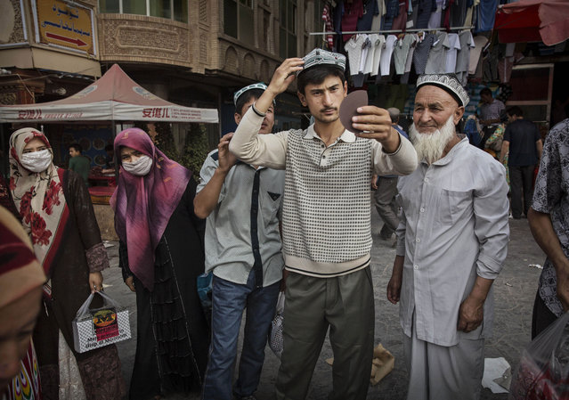 A Uyghur man tries on a new traditional hat as he buys new clothes before the Eid holiday  on July 28, 2014 in old Kashgar, Xinjiang Province, China. (Photo by Kevin Frayer/Getty Images)