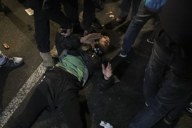 A demonstrator lies on the ground after falling during clashes after a protest for missing activist Santiago Maldonado, in Buenos Aires, Argentina, Friday, September 1, 2017. (Photo by Joaquin Salguero/AP Photo)