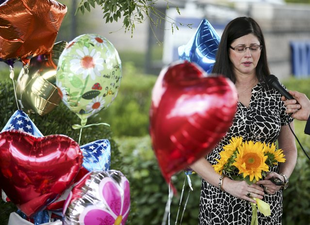 """A woman speaks with a journalist as she is overcome with emotions near a memorial outside of the offices for WDBJ7 in Roanoke, Virginia, August 26, 2015. Two television journalists were killed during a live broadcast in Virginia on Wednesday, shot by a suspect who was a former employee of the TV station and who called himself a """"powder keg"""" of anger over what he saw as racial discrimination at work and elsewhere in the United States. (Photo by Chris Keane/Reuters)"""