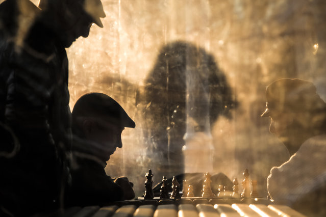 Men play chess, lit by the setting sun, while others watch in a park in Bucharest, Romania, Wednesday, January 1, 2020. (Photo by Vadim Ghirda/AP Photo)