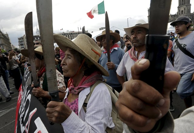 Mexican farmers and activists hold up machetes during a protest to mark the eleven-month anniversary of their disappearance of the 43 missing students of the Ayotzinapa teachers' training college, in Mexico City, Mexico August 26, 2015. (Photo by Henry Romero/Reuters)