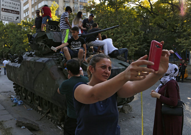 A woman takes a selfie in front a damaged Turkish military APC that was attacked by protesters near the Turkish military headquarters in Ankara, Turkey, Saturday, July 16, 2016. (Photo by Hussein Malla/AP Photo)