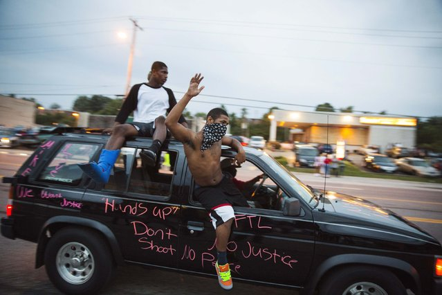 Protesters hang out of a car as they honk their horn and chant during ongoing demonstrations in reaction to the shooting of Michael Brown in Ferguson, Missouri August 16, 2014. Missouri Governor Jay Nixon declared a state of emergency and imposed a curfew in Ferguson on Saturday following a week-long series of racially charged protests and looting over the shooting of the unarmed black teenager by a white police officer. (Photo by Lucas Jackson/Reuters)