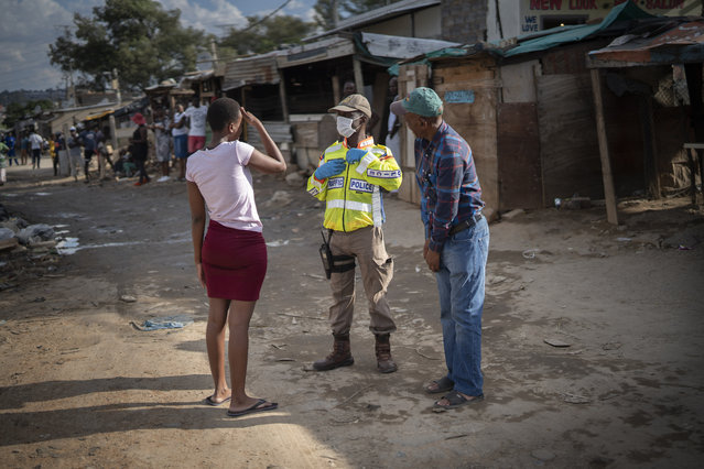 A South African police officer speaks to residents of the densely populated Alexandra township east of Johannesburg Friday, March 27, 2020. (Photo by Jerome Delay/AP Photo)