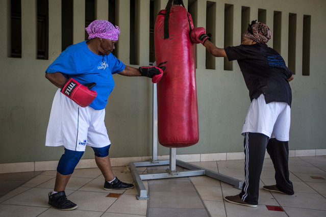 "77 year-old Gladys Ngwenya (R) and 79 year old Constance Ngubane use a punch bag as they take part in a ""Boxing Gogos"" (Grannies) training session hosted by the A Team Gym in Cosmo City in Johannesburg on September 19, 2017. (Photo by Gulshan Khan/AFP Photo)"
