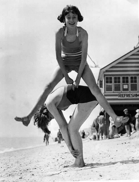 Two girls play leap-frog on the beach at Clacton. 27th June 1936.