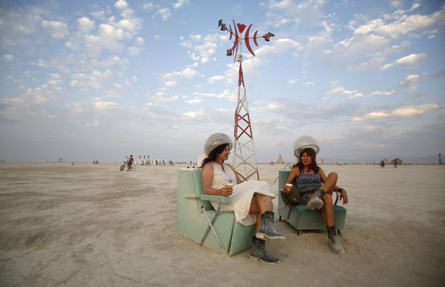 "Rosanne Ziering (L) and Alison Cooper relax on the Playa during the Burning Man 2014 ""Caravansary"" arts and music festival in the Black Rock Desert of Nevada, August 28, 2014. (Photo by Jim Urquhart/Reuters)"