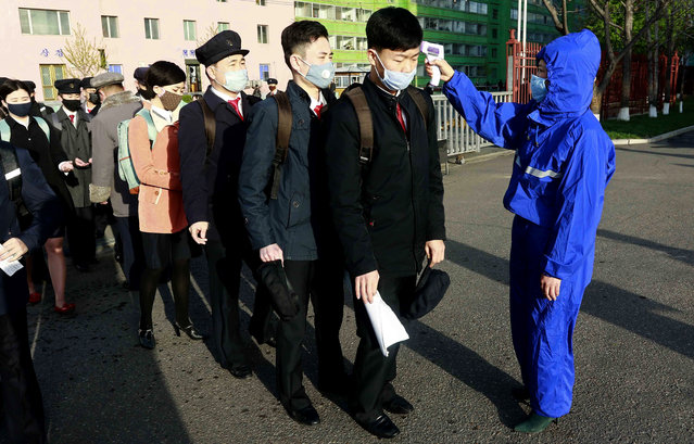 Students wearing a face mask have their temperature checked as a precaution against a new coronavirus as their university reopened following vacation, at Kim Chaek University of Technology in Pyongyang, Wednesday, April 22, 2020. (Photo by Jon Chol Jin/AP Photo)