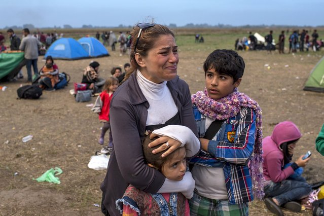 A migrant from Syria cries as she stands with her children on a field after crossing into Hungary from the border with Serbia near the village of Roszke, September 5, 2015. (Photo by Marko Djurica/Reuters)