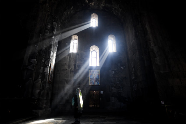 A woman prays in the Sts. Paul and Peter church at the 9th century Tatev monastery of the Armenian Apostolic Church some 270 km of Yerevan on October 8, 2017. (Photo by Kirill Kudryavtsev/AFP Photo)