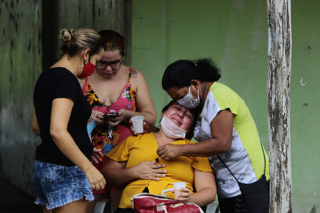 Relatives mourn while awaiting the removal of the body of Arlen Laranjeira Bezerra, 39, a victim of the new coronavirus and who died in circumstances still unknown after fleeing the emergency room of the Delphina Rinaldi Abdel Aziz Hospital in Manaus, Amazonas state, Brazil, Tuesday, May 5, 2020. Bezerra was admitted to the hospital to undergo treatment for COVID-19 disease and after escaping from the hospital at dawn, his body was found by family members approximately 200 meters from the hospital. (Photo by Edmar Barros/AP Photo)