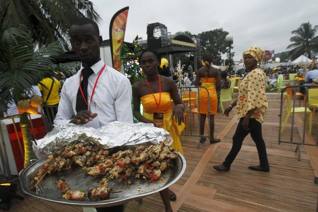 A man holds a plate with grilled meat during the Festival des Grillades, in the yard of the Culture Palace of Abidjan, September 5, 2015. (Photo by Luc Gnago/Reuters)