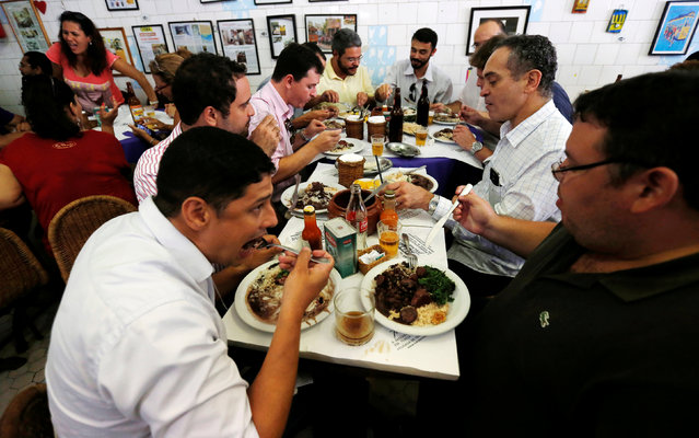 People enjoy the Brazilian traditional dish called feijoada (black bean and meat stew) at the Bar do Mineiro in Rio de Janeiro, Brazil, March 24, 2016. (Photo by Sergio Moraes/Reuters)