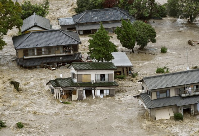 Residents are seen as they wait for rescue helicopters at a residential area flooded by the Kinugawa river, caused by typhoon Etau, in Joso, Ibaraki prefecture, Japan, in this photo taken by Kyodo September 10, 2015. (Photo by Reuters/Kyodo News)