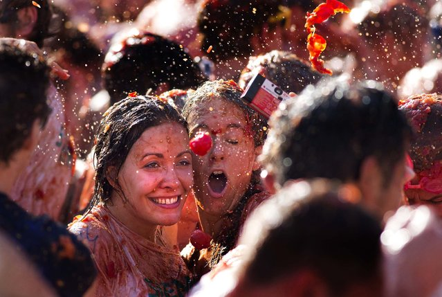 A tomato is about to hit two women taking a selfie during a tomato fight in front of the Royal Palace turning Amsterdam's central Dam square into a red pulpy mess Sunday, September 14, 2014. Entrepreneurs have seized upon Russia's boycott of European produce to set up a tomato-throwing fight. (Photo by Peter Dejong/AP Photo)