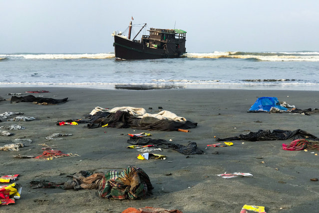 "Belongings of Rohingya refugees lay on the shore as their carrier boat remains anchored nearby in Teknaf on 16 April 2020. Thirty-two Rohingya died on an overcrowded fishing trawler stranded in the Bay of Bengal for nearly two months, officials said April 16 after hundreds of ""starving"" people were rescued from the vessel. (Photo by Suzauddin Rubel/AFP Photo)"