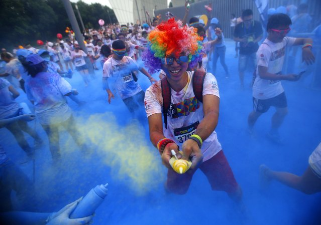A competitor has coloured powder sprayed at him during the Color Run in Shanghai September 27, 2014. Inspired by the Hindu Holi festival, participants take part in a five-km (3.11-mile) run dotted with locations where coloured powders are thrown over them. (Photo by Carlos Barria/Reuters)