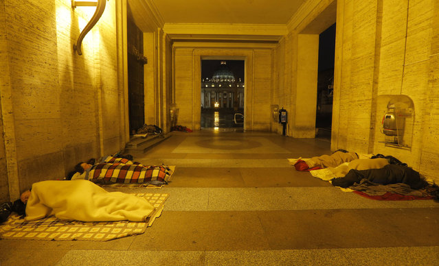 """This March 12, 2013 file photo shows homeless people sleeping near St. Peter's Square, with St. Peter's Basilica in the background. Pope Francis this summer is treating dozens of Rome's homeless to a day at the beach and dinner in a pizzeria on the way back. The pontiff's almsgiver, Polish monsignor Konrad Krajewski, told Italian state radio Sunday, August 14, 2016, the afternoon outings reflect the homeless' """"desire for normality"""" in their lives. The Vatican supplies the swimsuits and beach towels. (Photo by Dmitry Lovetsky/AP Photo)"""