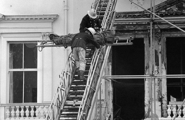 Firemen removing one of two bodies so far found in the burnt-out remains of the Iranian Embassy in London on May 7, 1980. The corpse, wrapped in a dark green body bag, was lowered from a second floor front window of the building in Princes gate, Kensington, and taken away by a hearse. (Photo by PA Images via Getty Images)