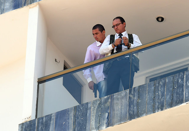 An unidentified man(L) keeps a hotel employee with an explosive-laden vest at a balcony of the hotel in Brasilia on September 29, 2014. (Photo by Evaristo Sa/AFP Photo)