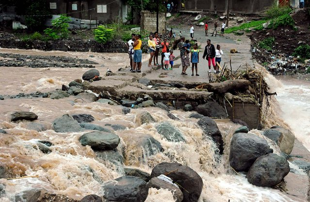 Residents stand on a bridge that was previously destroyed in 2008 by Tropical Storm Gustav, while watching Hope River swell in the village of Kintyre, near Kingston, Jamaica, after the passing of Hurricane Sandy on Thursday. Sandy, which made landfall Wednesday afternoon near Kingston, crossed over Jamaica killing an elderly man when a boulder crashed into his clapboard house, police said. (Photo by Collin Reid/Associated Press)