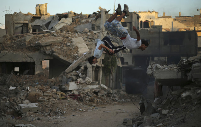 Palestinian youths practice their Parkour skills near the ruins of houses, which witnesses said were destroyed during a seven-week Israeli offensive, in the Shejaia neighborhood east of Gaza City October 1, 2014. (Photo by Mohammed Salem/Reuters)