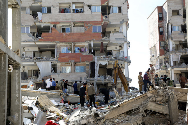 Civilians and soldiers search for the possible survivors trapped under the debris in Sarpol-e Zahab town of Kermanshah, Iran on November 13, 2017 following a 7.3 magnitude earthquake that hit the Iraq and Iran. (Photo by Fatemeh Bahrami/Anadolu Agency/Getty Images)