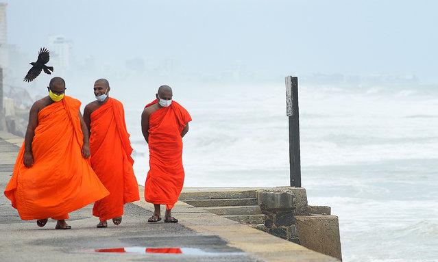 Buddhist monks walk along the Galle Face Green promenade in Colombo on May 22, 2020. (Photo by Ishara S. Kodikara/AFP Photo)