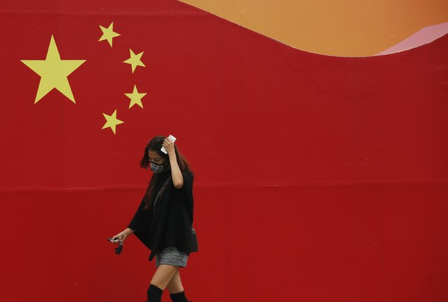 A woman wearing a mask walks past a wall painted with China's national flag in central Beijing, October 9, 2014. (Photo by Kim Kyung-Hoon/Reuters)