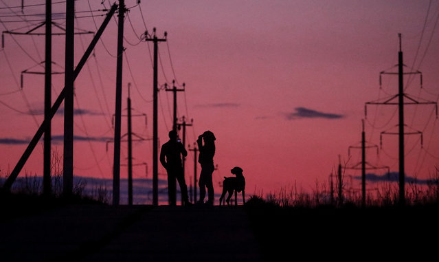 A couple take a walk with a dog at sunset in Moscow, Russia, 27 April 2020, during a lockdown implemented to stem the spread of the SARS-CoV-2 coronavirus that causes the COVID-19 disease. Russian authorities extended a home quarantine measure until the end of April 2020, reports state. (Photo by Sergei Ilnitsky/EPA/EFE)