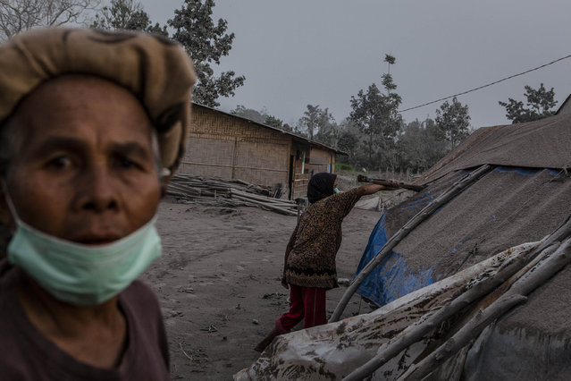 Kalem (R),  cleans her temporary tent as their village is hit by ash from the eruption of Mount Sinabung on October 13, 2014 in Berastagi, Karo district, North Sumatra, Indonesia. (Photo by Ulet Ifansasti/Getty Images)