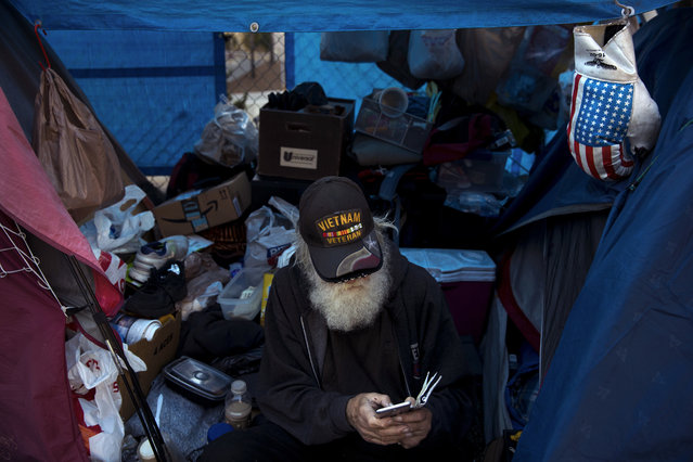 "Theodore Neubauer, a 78-year-old Vietnam War veteran, who is homeless, looks at his smartphone while passing time in his tent Friday, December 1, 2017, in Los Angeles. ""Well, there's a million-dollar view"", said Neubauer on what it's like to be homeless in Los Angeles. Neubauer has a tent pitched in the heart of downtown Los Angeles and is surrounded by high-rise buildings. (Photo by Jae C. Hong/AP Photo)"