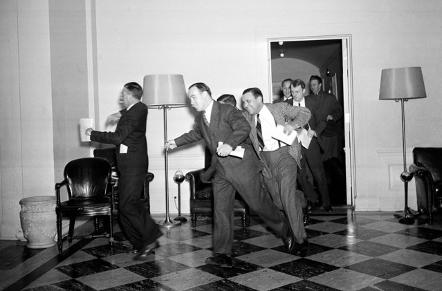 White House reporters dash for telephones after they had been told by presidential press secretary Stephen T. Early that Japanese submarines and planes had just bombed the U.S. Pacific fleet at Pearl Harbor. (Photo by Associated Press)