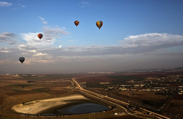 Hot air balloons soar over the Jezreel Valley in northern Israel during an international hot air balloon festival October 14, 2014. (Photo by Nir Elias/Reuters)